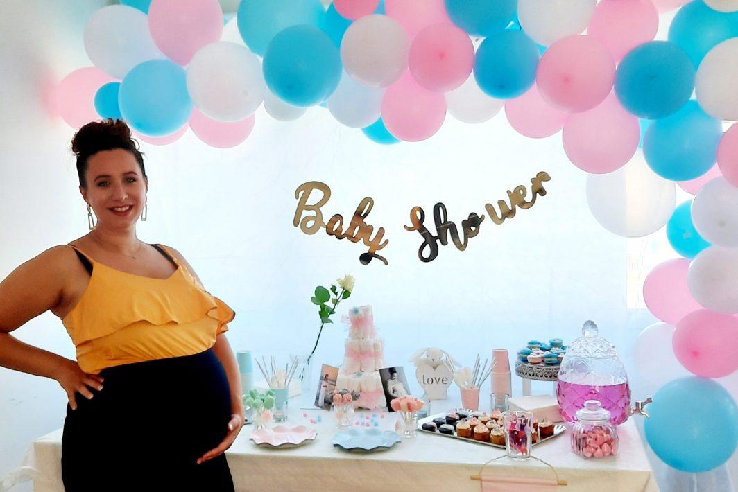 Future maman à sa baby shower devant son buffet candy bar. R'eva deux wedding et event planner nantes
